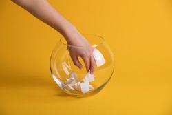 Hand randomly picking a winner from a glass bowl. Random name ballot, simple raffle