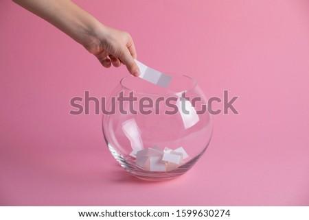 Hand randomly picks a winner from a glass bowl, random name ballot, simple raffle