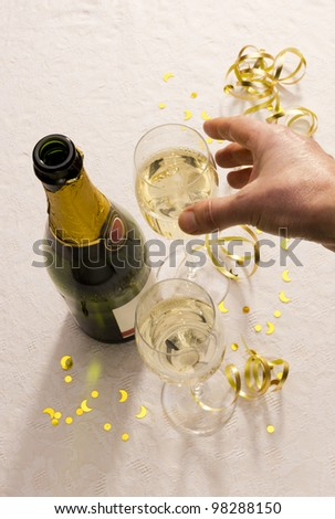 Hand reaches for champagne glasses beside bottle on party table with copy space.