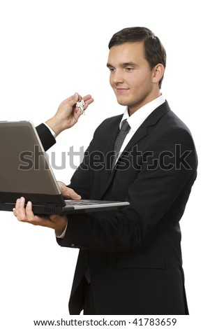 hand reaches out of laptop towards young businessman holding