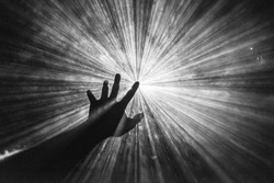 Hand reaches out to touch the light