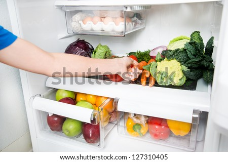 Hand Reaching for Carrot in Refrigerator Full of Healthy Food Options