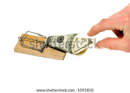 Hand reaching for dollar bill in mousetrap - stock photo