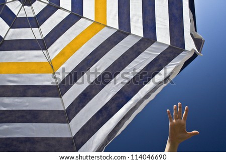 Hand reaching for striped parasol - stock photo