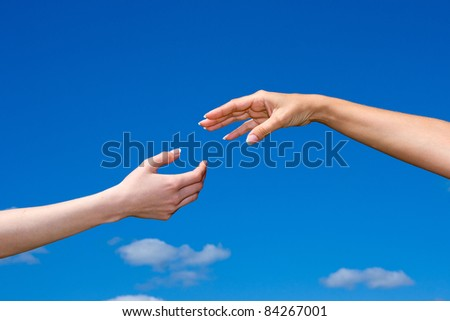 Hand reaching out from the blue sky