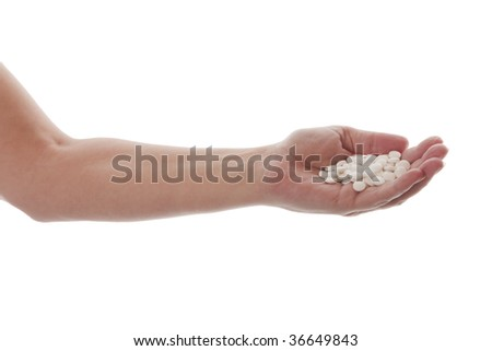Hand reaching out with a handful of white pills