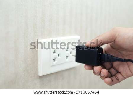 Hand ready to plug or unplug  black power cord cable mobile phone charger charts Into electric socket on wall. Ready to connect plugging electrical. power saving or cost reduction concept. soft focus. Сток-фото ©