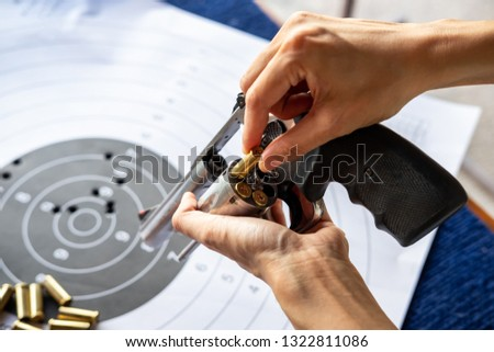 Hand reloading pistol revolver with bullets and target #1322811086