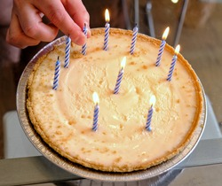 Hand removing one of the Birthday candles on a key lime pie. High angle. Birthday pie