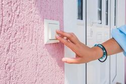 hand ringing on doorbell on pvc front door