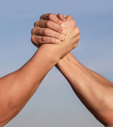 Hand rivalry vs challenge strength comparison. Man hand. Two men arm wrestling. Arms wrestling. Closep up. Friendly handshake, friends greeting, teamwork, friendship. Handshake, arms, friendship.