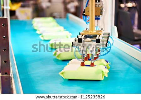 Hand robot manipulator for packaging products on conveyor #1125235826
