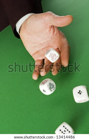 Hand rolling dices on green table close up