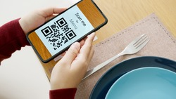 Hand's customer scan QR code for online menu service at table in restaurant during pandemic coronavirus. New normal contactless technology lifestyle protection coronavirus pandemic in restaurant
