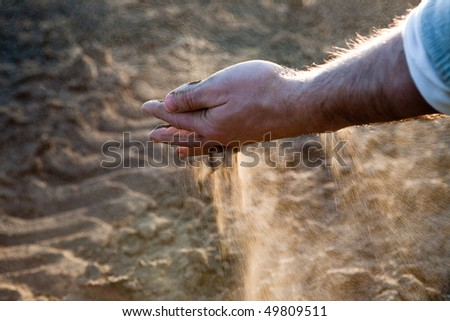 Hand's man throwing dry earth, against the light