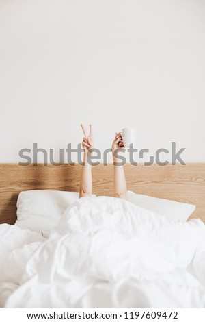 Hand's of young woman with coffee mug in bed with white linens. Minimal happy morning concept.