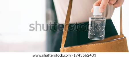 Hand sanitizer travel bottle woman carrying in purse COVID-19 prevention alcohol gel for cleaning hands while outside doing errands. Coronavirus virus pandemic banner panoramic header.