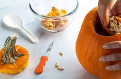 Hand scooping pumpkin seeds out of a pumpkin to prepare it for carving for Halloween.