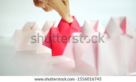 Hand selecting a one Red among white origami shirt paper , unique individuality and difference or leadership and , Business recruitment human resource concept. #1556016743