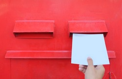 Hand sending a letter or postcard in a red Postbox.
