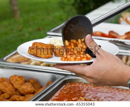 Hand serving a plate of beans and nuggets with a plastic spoon in a picnic setting