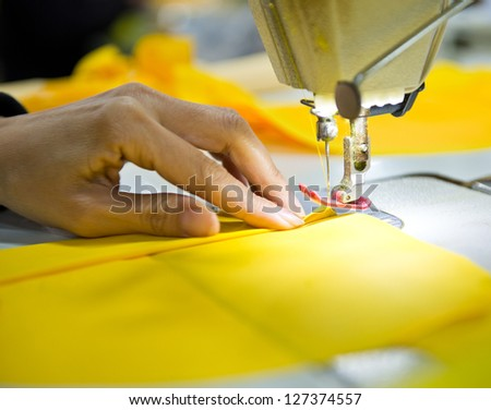 Hand sewing a material on a machine.