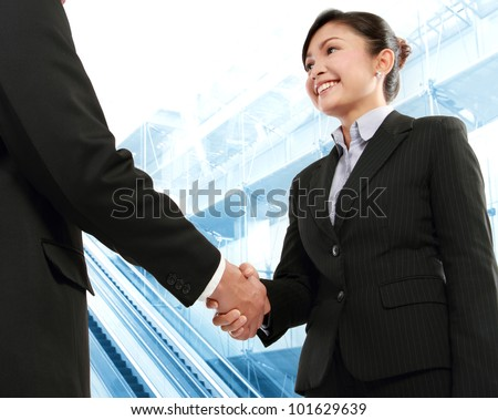 Hand shake between a businessman and a businesswoman in office environment