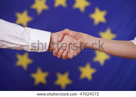 hand shake in front of a waving european flag