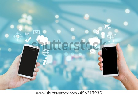 Hand show or present big blank screen mobile or cellphone or smartphone on blurred event hall,transferring data or business cantact,business to business ,e-commerce