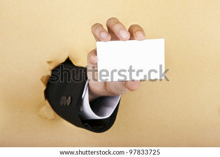 Hand showing a blank business card breaking through a paper wall