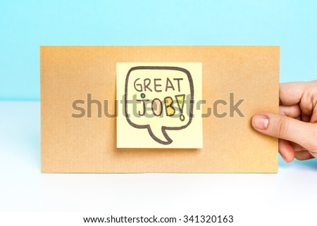Hand showing a cardboard with post-it note exclaiming great job!