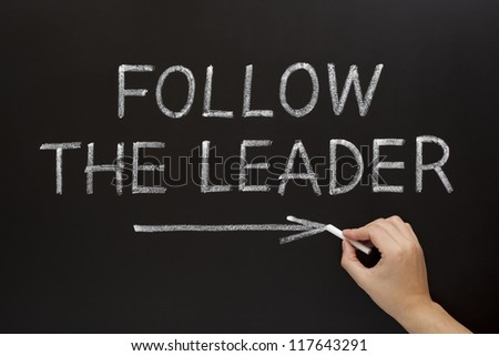 Hand showing Follow The Leader written with white chalk on a blackboard