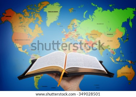 Hand showing the Holy Bible against world map Stock photo ©