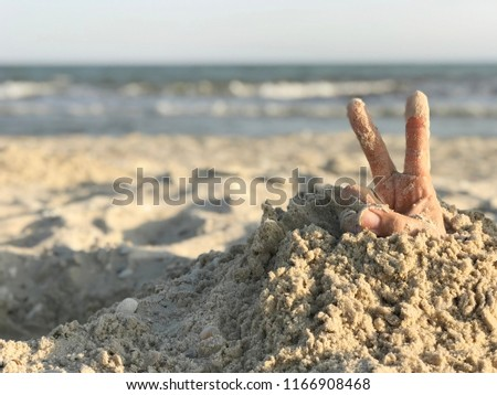 Hand showing the sign of victory and peace closeup. Hands buried in sand on a beach.