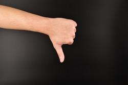hand showing thumbs down gesture on dark background