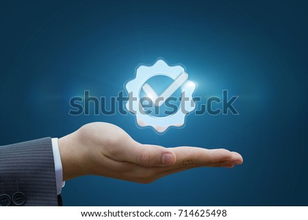 Hand shows the sign of the top service on the blue background .