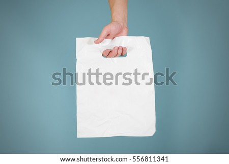 Hand shows white blank plastic bag mock up isolated. Empty white polyethylene package mockup. Consumer pack ready for logo design or identity presentation. Commercial product food packet handle