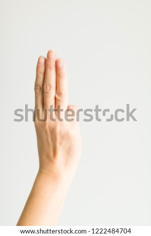 Hand sign showing three fingers (index finger, middle finger and ring finger) on white background.