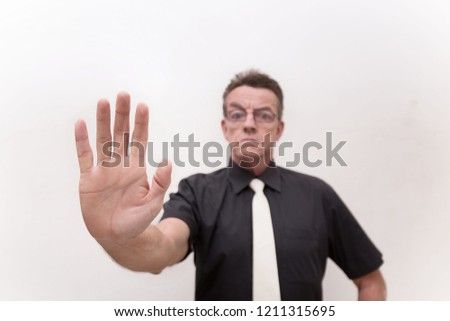 hand signal stop with serious face and strict gesture from strict man in black cloth and white tie on white background #1211315695