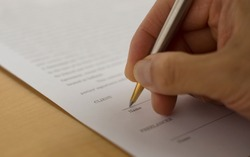 hand signing a document with pen. Signing a contract. Hand holding a pen.