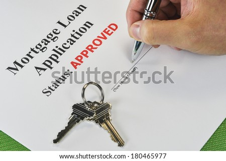 Hand Signing An Approved Real Estate Mortgage Loan Document With House Keys