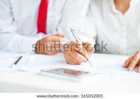 hand signing documents (soft focus on a pen)