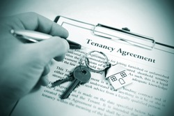 Hand signing tenancy agreement on clipboard with keys and symbolic house keyring