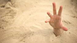 Hand sinking in quicksand, trying to get out, tips to survive in desert, buried