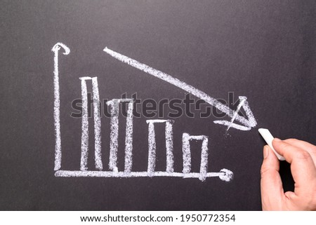 Hand sketching decreasing graph on chalkboard, business going down, decrease sales and revenue in economic crisis Сток-фото ©