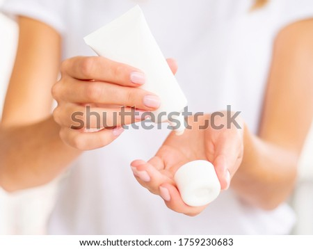 Hand Skin Care. Feminine Hands Holding opened Cream Tube and Applying white Cosmetic Cream On Silky Healthy Skin. Copy space on a white jar. Front view mockup Сток-фото ©