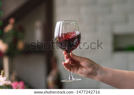 Hand sommelier holding glass of red wine. Swirling red wine glass in wine tastings. Wine tour. Space for text.  Foto stock ©