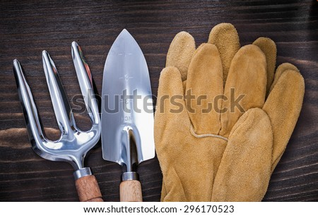 Hand spade trowel fork and leather safety gloves on vintage wooden background gardening concept.