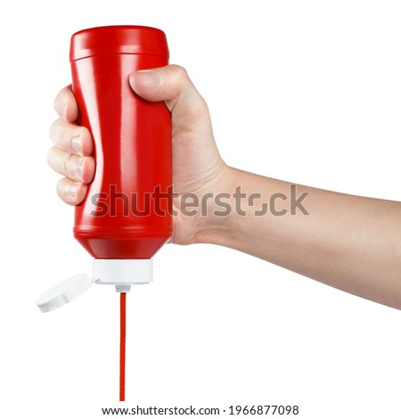 Hand squeezing ketchup out of a plastic bottle, isolated on white background Stockfoto ©