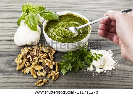 Hand stirring homemade pesto with basil, garlic, walnuts and parsley on aging wood background